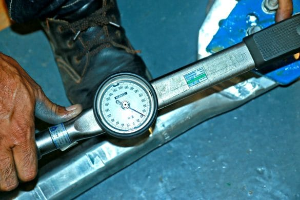 Man using torque wrench with dial to tighten bolt